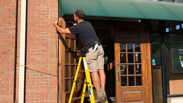 Sanding wood doors on retailer entrance