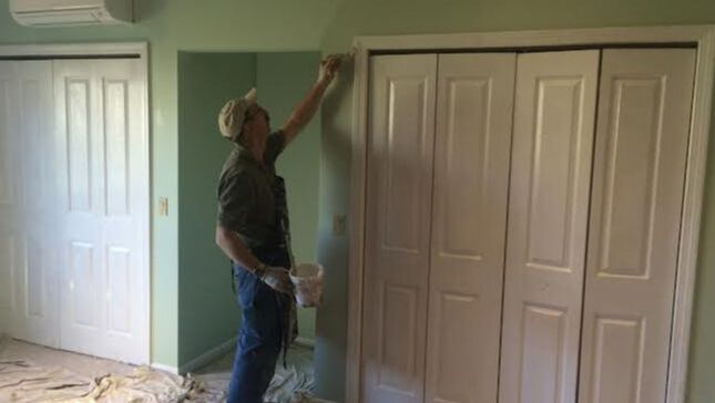Contractor painting white trim around closet door